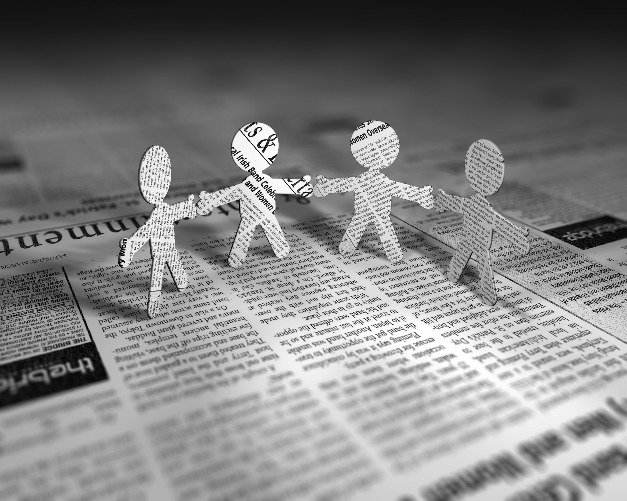 newspaper cutout people holding hands
